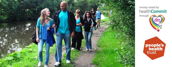 Image of people walking in the countrysdie with sighted guides smiling and talking. The people's health trust logo is alongside the image.