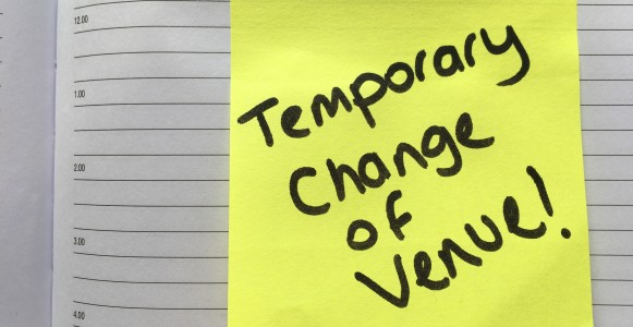 Image of a yellow sticky note with the words 'Temporary Change of Venue!' written in black marker pen. The Yellow sticky note is stuck to a diary page.