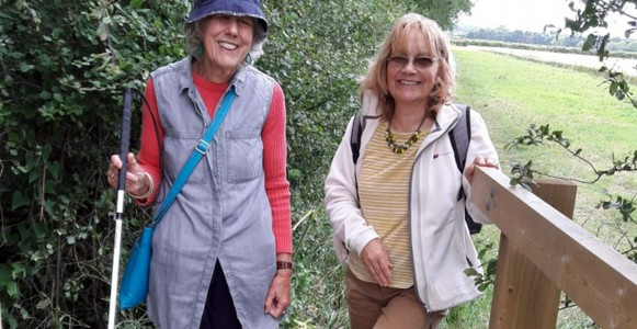 Image of two ladies stood in the countryside at the bottom of a footbridge looking at the camera. The lady on the left has a white cane. Both ladies are smiling.
