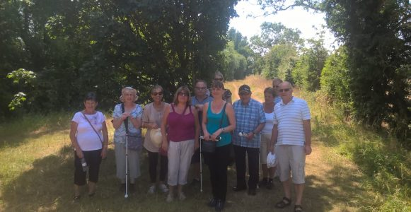 Image of visually impaired members in the countryside on a hot sunny day with volunteers standing in a group facing the camera