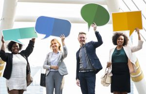 People Holding Up Speech Bubbles Smiling Pab