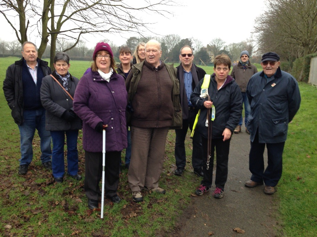 Pictured are approximately 9 people of the PAB walking group standing on a field and path on a winters day smiling for the camera